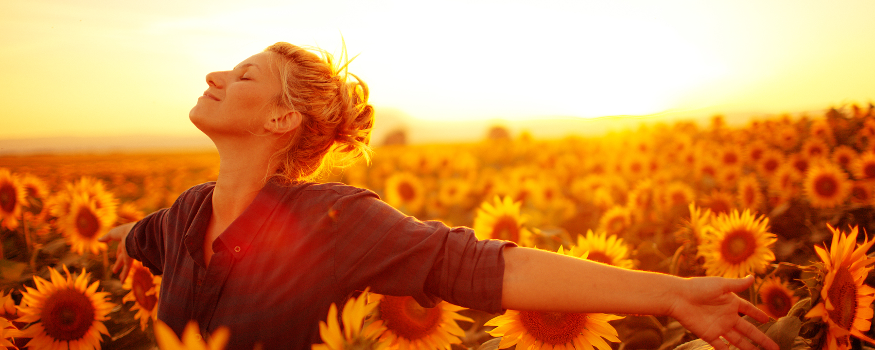 image of woman standing with arms open in a sunflower field
